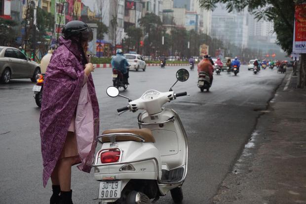 Một cô gái dừng xe ở đường để mặc áo mưa.