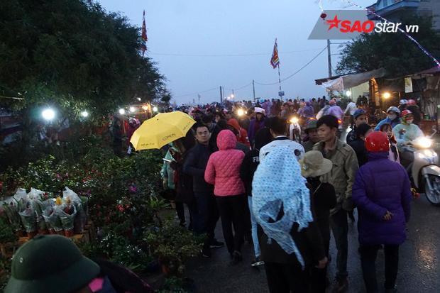 """Trời đổ mưa cũng không ngăn được dòng người đổ đến chợ Viềng """"mua may bán rủi""""."""