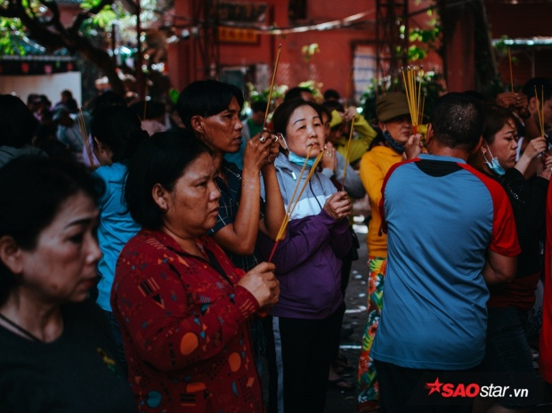 Chờ đợi khá lâu không chen chân được vào trong chùa, nhiều người đốt hương khấn vái ngay tại ngoài điện.
