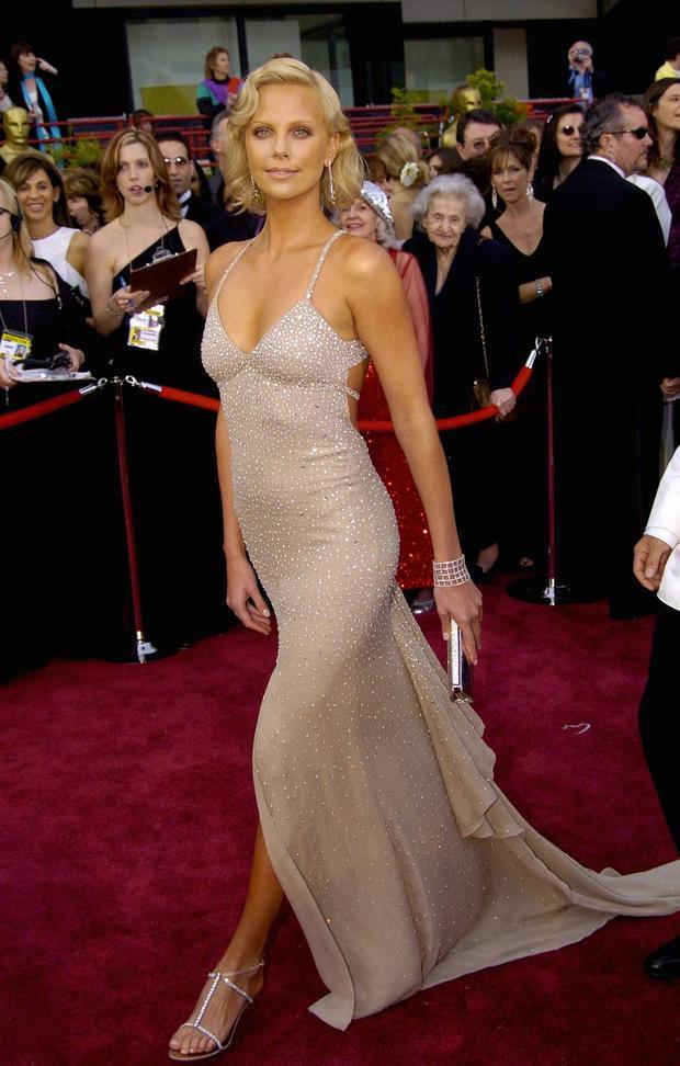 Charlize Theron tỏ sáng trong chiếc váy Gucci do Tom Ford thiết kế, khi cô nhận giải Nữ diễn viên xuất sắc nhất cho vai diễn giết người hàng loạt trong bộ phim 'Monster'. Cô trông thật tuyệt trong bộ trang phục lộng lẫy này với giày gót kim loại, một chiếc vòng bằng kim cương và một chiếc clutch màu bạc trên tay.