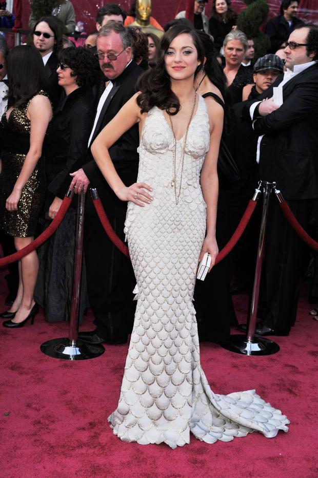 Nữ diễn viên người Pháp Marion Cotillard đã mặc chiếc đầm thiết kế couture từ nhà mốt Jean-Paul Gauthier đến nhận giải Nữ diễn viên xuất sắc nhất cho phim 'La Vie an Rose'. Cô khéo kéo kết hợp chiếc đầm với chiếc vòng cổ dài và chiếc clutch màu trắng nhẹ nhàng.