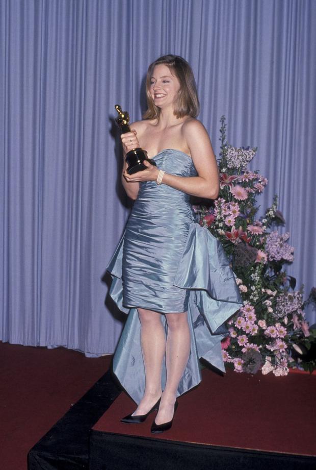 """Jodie Foster đã diện chiếc váy đuôi cá có chất liệu satin màu xanh này vào đêm trao giải năm 1989. Chiếc váy này được cô tình cờ phát hiện ở thành phố Rome và cô không ngại ngần mua ngay lập tức. Bên cạnh váy áo lộng lẫy, Foster thật sự trở thành nữ hoàng trong đêm đó khi được trao giải thưởng Nữ diễn viên xuất sắc nhất với vai diễn trong phim """"The Accused""""."""