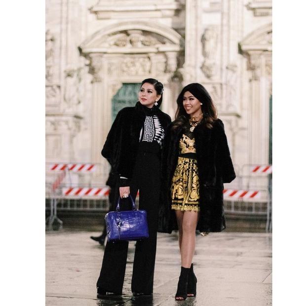 Tuy người diện váy, người mặc áo kiểu họa tiết cùng quần cạp cao ống suông, nhưng cả hai mẹ con doanh nhân đều khoác áo choàng đen đồng điệu.