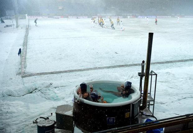 Ba cô gái mặc bikini tắm bồn vừa xem rận đấu trong lúc tuyết rơi dày.