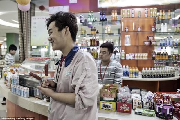 Một công nhân mua hai chiếc xúc xích trong canteen nhà máy.