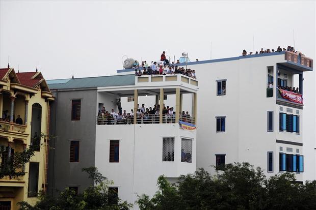 Nhiều người dân phải trèo lên ban công các căn nhà cao tầng để theo dõi lễ hội.