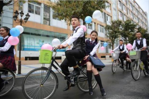 """Các nam sinh thuê xe đạp có gắn bóng bay để chở nữ sinh tới trường trong """"Ngày con gái""""."""