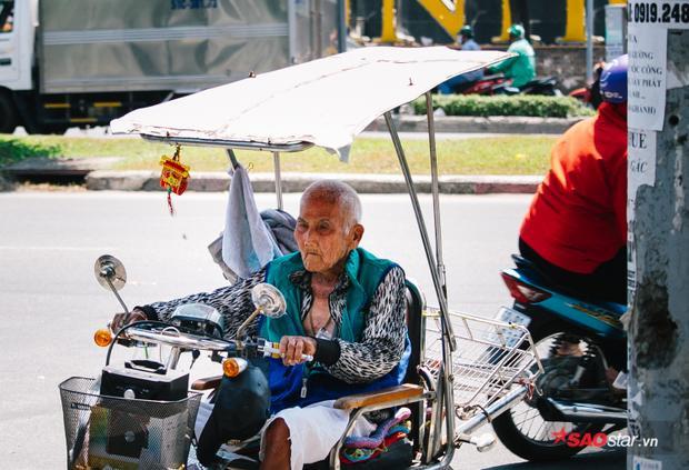 Một cụ ông bán vé số trên đường Nguyễn Hữu Cảnh phải lắp tạm thêm mái che nắng trên xe máy.