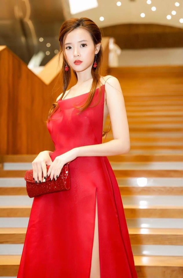 Ngoài ra, ví cầm tay đỏ ánh kim cũng góp phần hoàn thiện trang phục hơn.