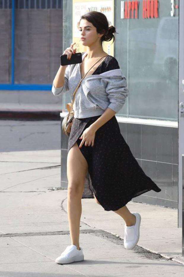 Nếu không biết diện trang phục thể thao như thế nào để vừa đẹp, vừa thoải mái, cứ khoác thêm một chiếc áo bomber là sẽ ổn. Selena Gomez đã khiến nhiều người ngạc nhiên khi diện chiếc váy wrap nữ tính phối cùng áo khoác nỉ màu xám, đi cùng đôi sneaker trắng hợp tông.