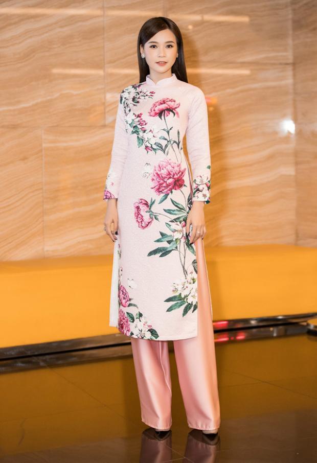 Nổi bật giữa dàn mỹ nhân xúng xính váy áo, Sam đem đến cái nhìn nhẹ nhàng rất đỗi Á Đông với tà áo dài hồng in họa tiết hoa. Mái tóc và phụ kiện của cô nàng hot girl cũng được tiết chế để phù hợp với tổng thể.