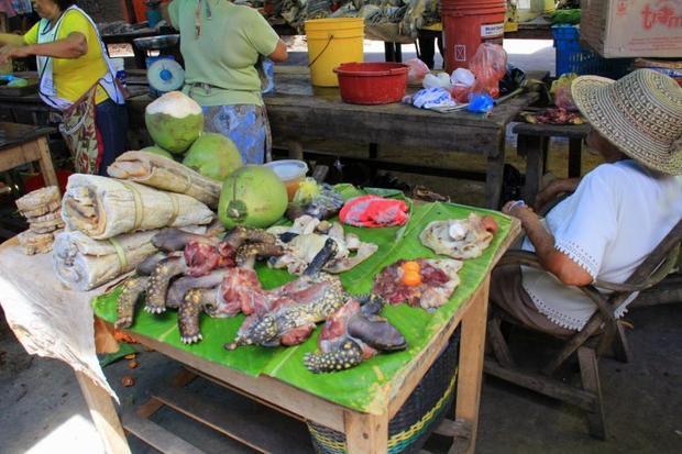 Các loại thịt được bày bán chung trên một chiếc bàn, bên cạnh là nhiều sản phẩm khác như trái cây… Ảnh: Go no mad