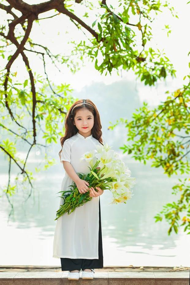 Chỉ là mặc áo dài chụp với hoa loa kèn thôi, mà mẫu nhí này đã chiếm hết spotlight rồi