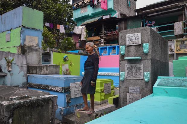 """""""Tôi đã sống ở đây 51 năm. Bây giờ chính phủ muốn chúng tôi rời đi, tôi cũng muốn chuyển chỗ ở lắm nhưng chưa biết phải đi đâu"""", bà Elvira Miranda, 68 tuổi, nói. Bà cùng chồng và các con sống ở nghĩa trang Navotas từ năm 1996."""