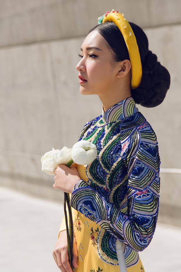Chiếc áo dài vàng với điểm nhấn là họa tiết xanh ở phần cổ và tay vừa tạo cảm giác trang nhã, vừa thể hiện sự quyền lực.