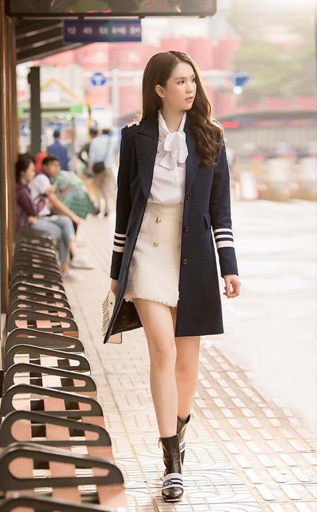 Ngọc Trinh phối chân váy trắng ngà cùng sơ mi, chiếc vest dáng dài tạo hình ảnh sang trọng đúng chất quý cô. Boots da là lựa chọn thích hợp cho trang phục này.