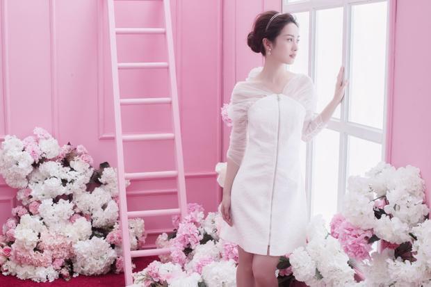 Jun Vũ thêm phần nữ tính trong thiết kế đầm trắng dịu dàng với phần tay áo được cách điệu.