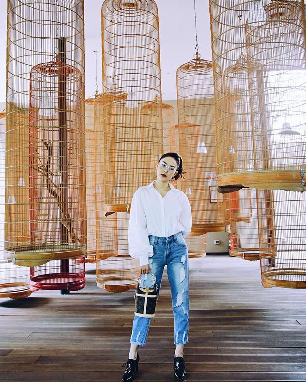 Để tôn lên chiếc túi Sac Duffle của Louis Vuitton trị giá hơn 50 triệu đồng, Minh Hằng lựa chọn set đồ đơn giản gồm áo sơ mi trắng cùng quần jeans rách.