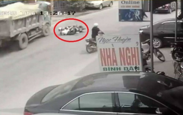 Hai nữ sinh ngã ra đường, ngay trước đầu xe tải. Ảnh cắt từ clip.