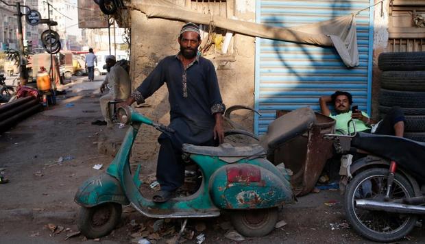 Một người đàn ông đứng bên cạnh chiếc xe Vespa cổ của mình.
