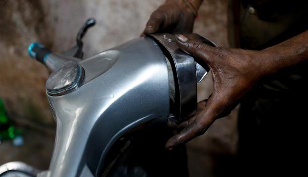 Một người thợ máy đang lắp ráp đèn cho chiếc xe Vespa cổ.