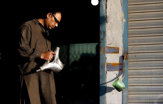 Một công nhân đang cố gắng khôi phục bộ phận của xe Vespa ở Islamabad.
