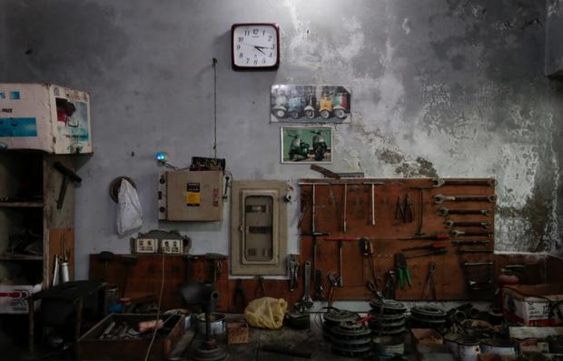 Các bộ phận và dụng cụ để sửa chữa cho Vespa cổ tại một xưởng sửa chữa xe máy.