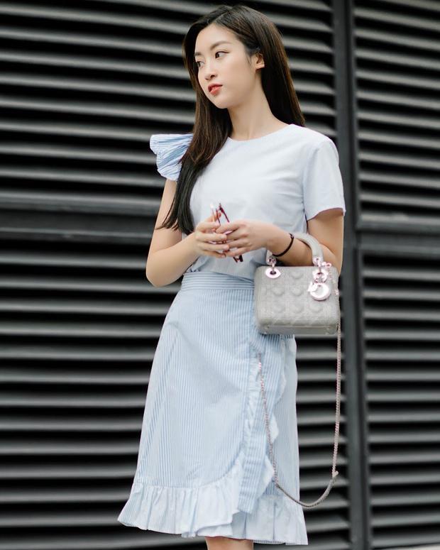 Đỗ Mỹ Linh khoe vẻ dịu dàng với áo kiểu và chân váy dún bèo. Hoa hậu Việt Nam 2016 cũng để kiểu tóc xõa đơn giản cùng mang túi Lady Dior màu nude để hoàn thiện tổng thể.