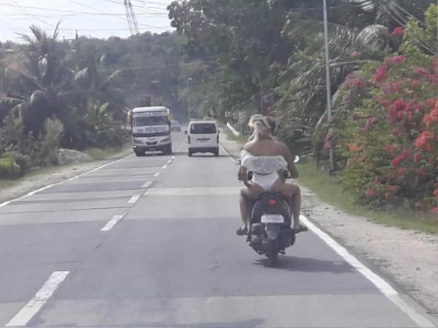 Cặp đôi ăn mặc phản cảm đi xe máy dạo trên đường phố.