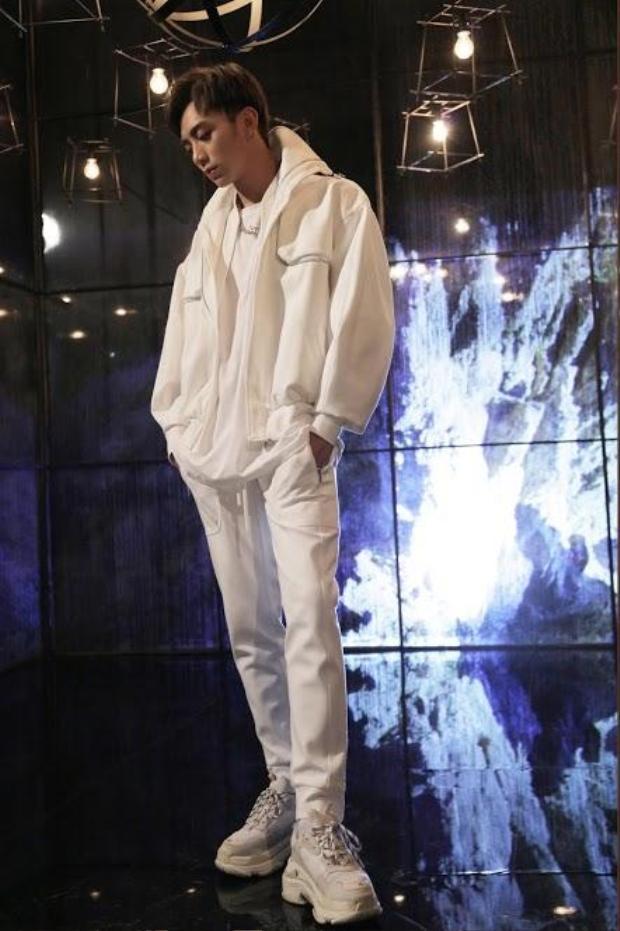 """Mở đầu MV là bộ cánh all-white được phối layer rất tài tình và ấn tượng. Với cách chọn dáng trang phục phom rộng, Soobin đã tạo nên một hình ảnh rất phóng khoáng nhưng cũng rất hợp với dáng vóc của mình.Màu trắng luôn khiến người mặc trông đầy đặn hơn, thêm form rộng trendy nữa là đủ combo """"ăn gian da thịt"""" tài tình cho nam ca sĩ. Và tất nhiên không thể thiếu được đôi giày đế thô - Balenciaga triple S cùng tông đình đám."""