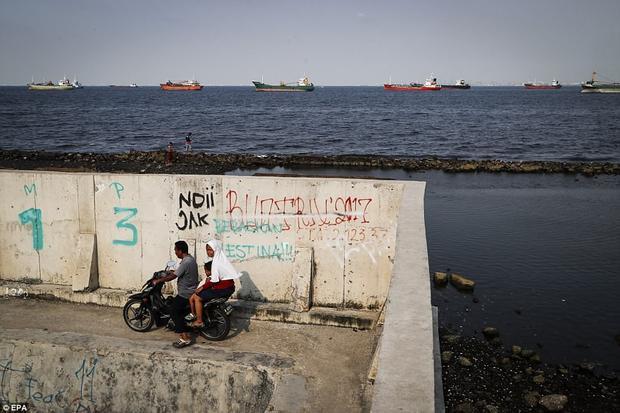 Một gia đình đang đi xe máy dọc theo bức tường biển trong khu vực Muara Baru, nơi đang đi đầu trong việc chống lũ lụt ở Jakarta.