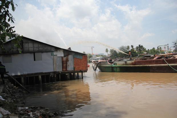 Các sà lan cát trên sông Bảo Định hỗ trợ dập lửa - Ảnh: Mậu Trường/Tuổi Trẻ.