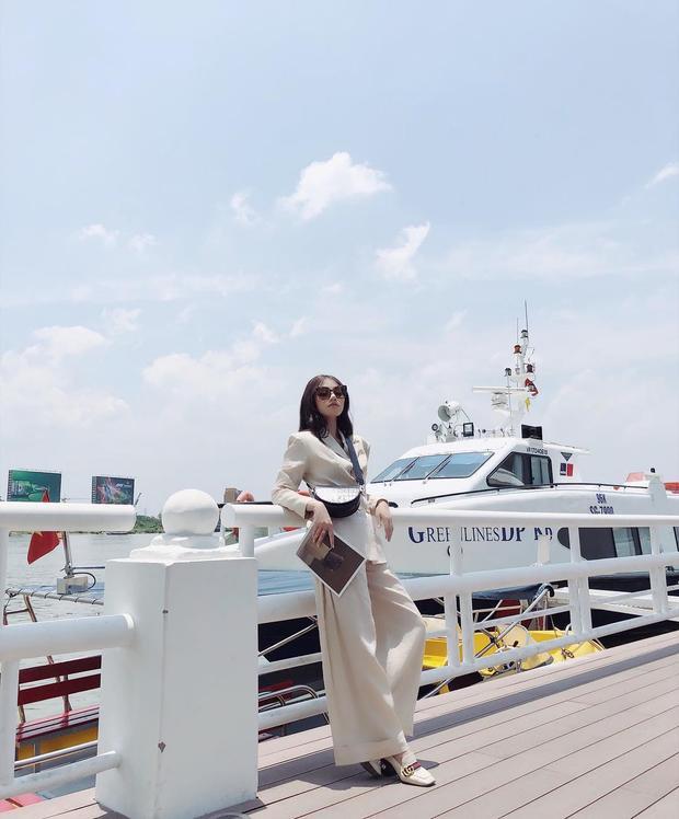 Jolie Nguyễn sang chảnh với cả cây đồ vest cùng quần ống loe màu kem. Người đẹp sử dụng kính mát cùng túi đeo chéo tông đen để nhấn nhá cho outfit.