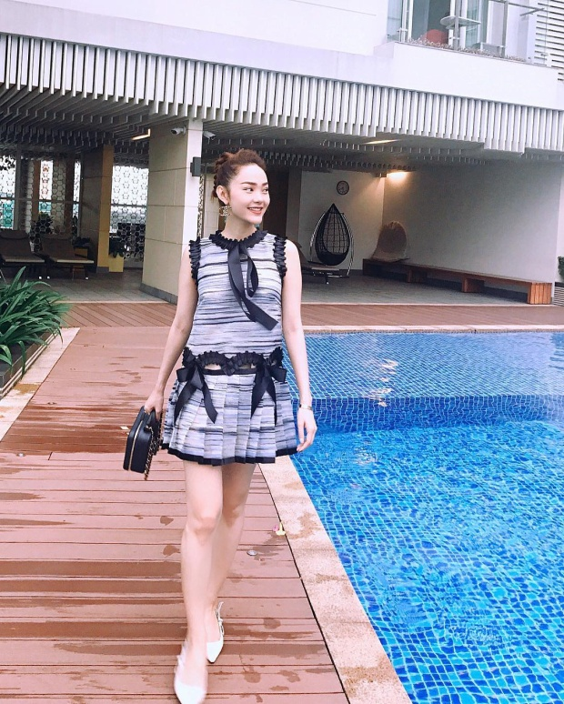 Minh Hằng thả dáng với váy ngắn xếp bèo với điểm nhấn là những chiếc nơ nhỏ xinh. Nữ ca sĩ mang giày trắng và túi đen dáng hộp để hoàn thiện tổng thể.