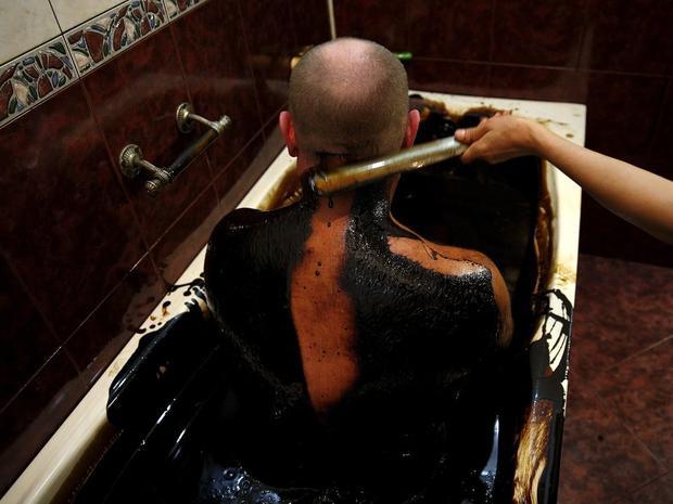 Tắm tráng sau khi ngâm mình trong dầu. Ảnh: Reuters