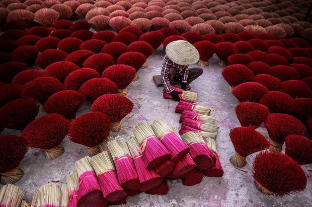 """Tác phẩm """"Làm hương"""" của tác giả Trần Tuấn Việt cũng xuất sắc chiến thắng ở hạng mục ảnh Du lịch. Bức ảnh được chụp tại Quảng Phú Cầu, Ứng Hòa, Hà Nội. """"Tại quốc gia Phật giáo như Việt Nam, hương là một phần không thể thiếu ở các lễ hội truyền thống hoặc nghi lễ tôn giáo"""", nhiếp ảnh gia cho hay."""