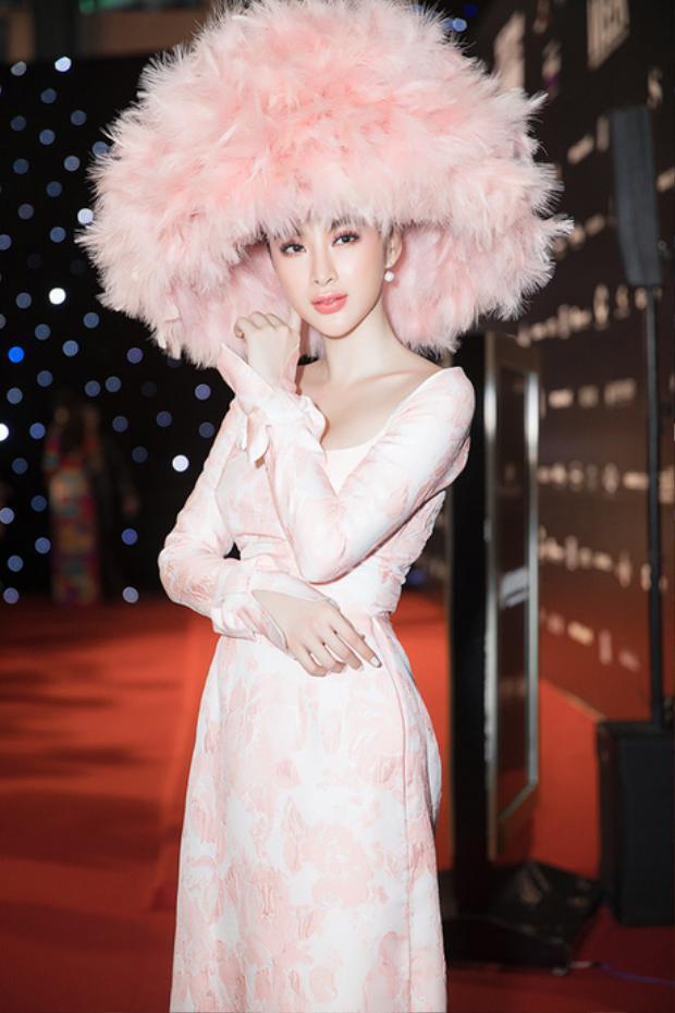 """Diện tà áo dài hồng cổ thuyền của NTK Công Trí, """"Bà mẹ nhí"""" hoàn toàn chiếm trọn spotlight khi đội chiếc mũ lông to cả mét."""