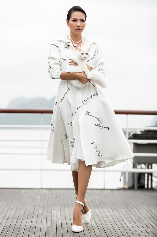 Diện bộ váy xòe bồng, tay ôm mèo trắng, Minh Triệu thảnh thơi dạo bước mở màn cho show diễn trên du thuyền của Lê Thanh Hòa.