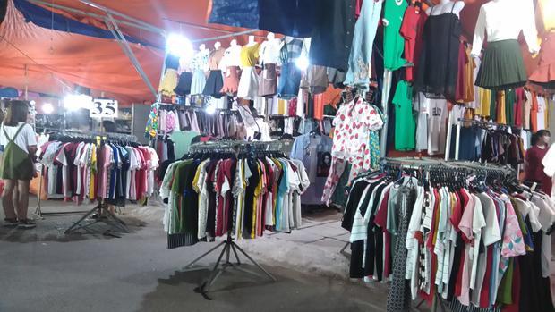 Quần áo đa dạng được sắp xếp gọn gàng trong chợ.