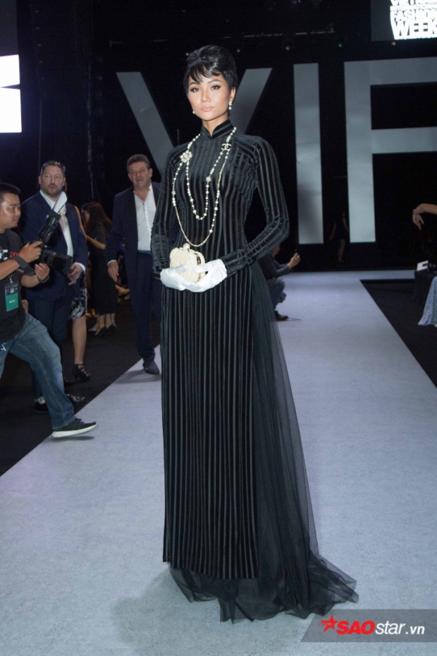 """Lần thứ 2 đến dự VIFW 2018, Hoa hậu H'Hen Niê chuyển mình sang hình ảnh """"mệnh phụ phu nhân"""" sang trọng đài các với bộ áo dài đen tuyền, tóc búi kiểu retro."""
