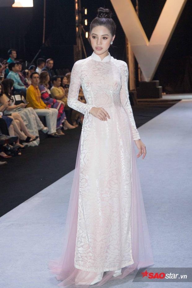 Jolie Nguyễn nổi bật với chiếc áo dài trắng có họa tiết nhẹ nhàng.