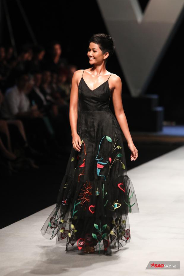 Cô trình diễn một thiết kế váy xòe nhẹ nhàng với phần tùng voan lưới đính sticker họa tiết khá trẻ trung.