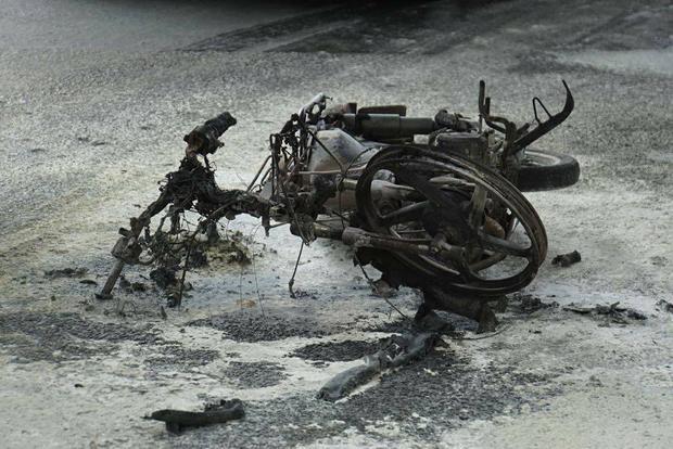 Xe máy cháy đen trơ khung trên đường.