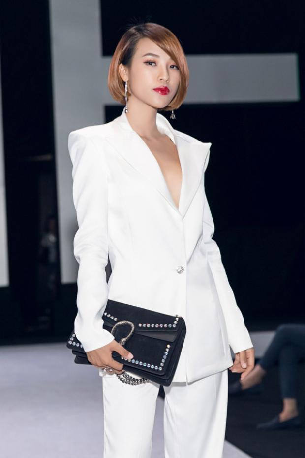 Cả cây vest trắng xẻ sâu giúp đem lại cho Hoàng Oanh vẻ ngoài thanh lịch. Bên cạnh đó, cô còn nhấn nhá bằng chiếc túi Gucci đen đính đinh tán, giúp hoàn thiện tổng thể.