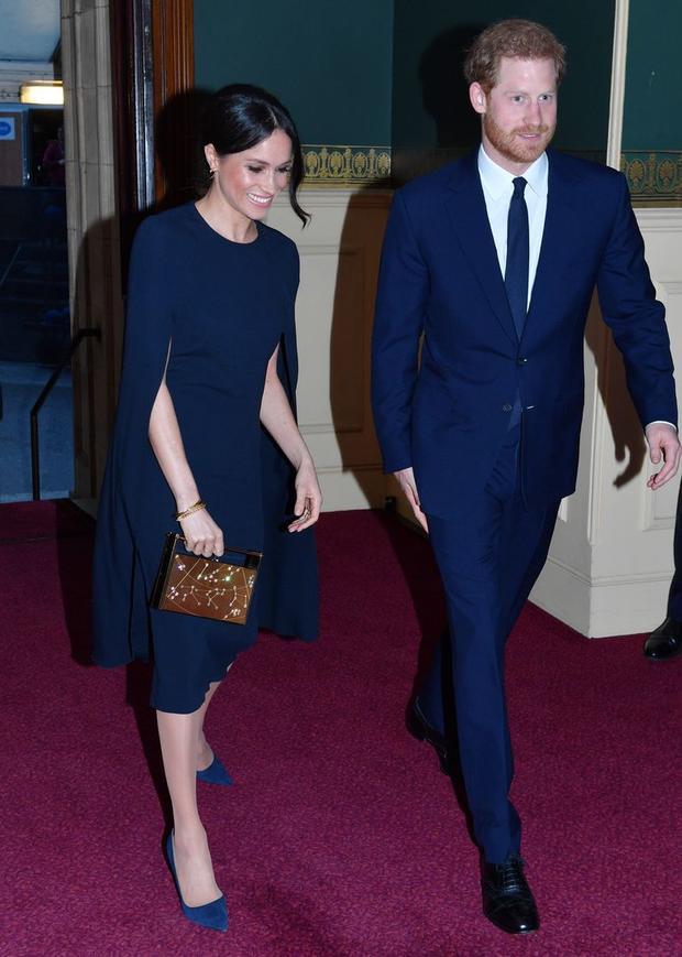 Trong tiệc sinh nhật nữ hoàng Anh, công nương tương lai Meghan Markle rạng rỡ sánh bước cùng hoàng tử Harry trong chiếc váy cape thanh lịch. Người đẹp kết hợp trang phục hiệu Stella McCartney với giày cao gót màu sắc đồng điệu và phụ kiện clutch hình hộp nổi bật.