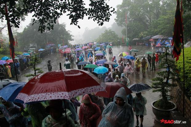 Dòng người mặc áo mưa, che ô tiến về phía trước hàng rào, chờ đợi để được vào bên trong dâng hương.