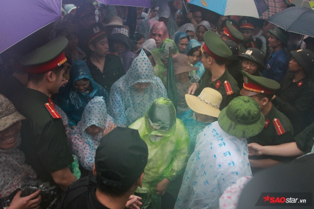 Tại các điểm chốt hàng rào trong khuôn viên đền, lực lượng chức năng cùng thanh niên tình nguyện vẫn đứng dưới mưa để đảm bảo an ninh cho lễ hội.