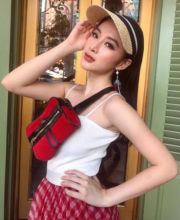 """Angela Phương Trinh cũng lựa chọn """"bảo bối"""" này, vừa giúp làm duyên, vừa chống lại những ánh nắng chói chang của mùa hè. Cô nàng mix cùng áo hai dây và chân váy xòe tông màu đỏ đi cùng túi fanny pack Gucci đồng điệu."""