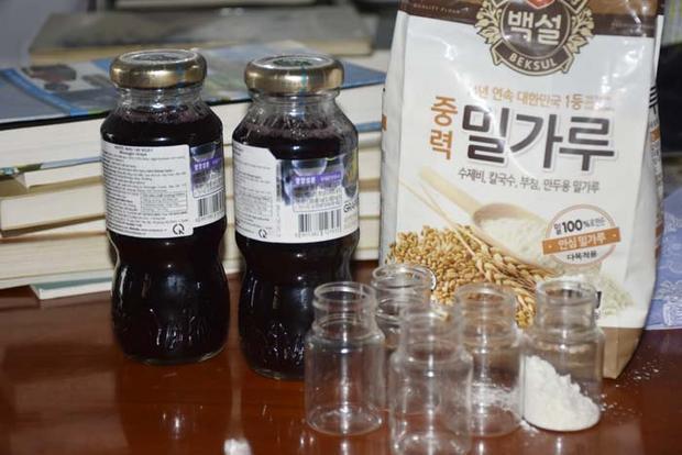 Nước màu đỏ và bột trắng dùng để cho hội viên uống khi gia nhập hội. Ảnh: Công an Thanh Hóa.