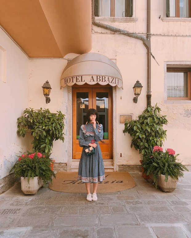 Ca sĩ Min trông như một tiểu thư trong chuyến đi du lịch đến Ý. Cô nàng chọn mặc một chiếc váy xòe có nơ bèo, phối cùng giày đế bệt và túi đéo để phù hợp với tổng thể.